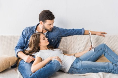 Photo for Attractive woman with digital tablet laying on knees of boyfriend on sofa at home - Royalty Free Image