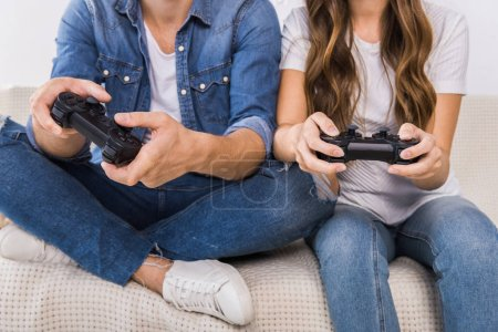 Photo for Cropped image of couple playing video game by joysticks on sofa at home - Royalty Free Image