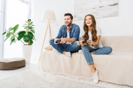 laughing couple playing video game by joysticks on sofa at home