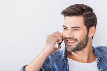 close up portrait of happy handsome man talking on smartphone and looking away at home