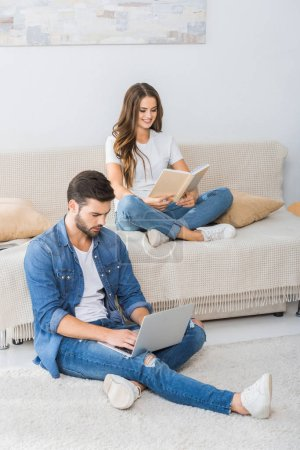 confident man with laptop sitting on floor while his girlfriend reading book on couch at home