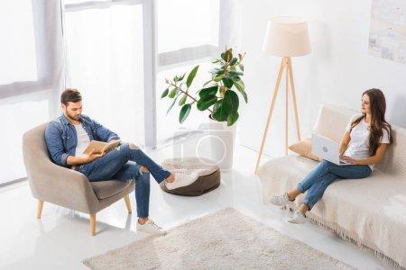 vue d'angle élevé de femme à l'aide d'ordinateur portable sur le canapé tandis que son livre de lecture de petit ami sur le fauteuil à la maison
