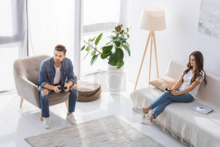 Photo for High angle view of concentrated young couple playing video game with joysticks at home - Royalty Free Image