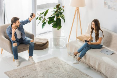 high angle view of smiling man with joystick gesturing by hands and celebrating victory while his upset girlfriend sitting near on couch at home