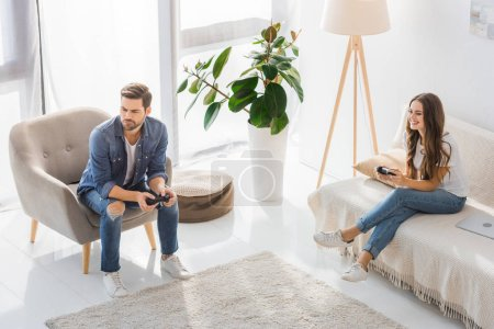 high angle view of upset young man playing video game with smiling girlfriend at home