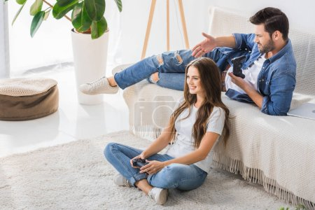 upset young man with joystick pointing by hand at smiling girlfriend sitting on floor at home