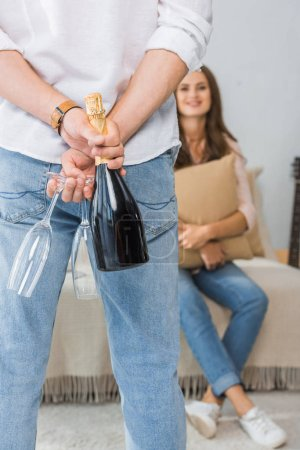 cropped image of man hiding bottle of champagne with glasses behind his back while his girlfriend sitting on couch at home