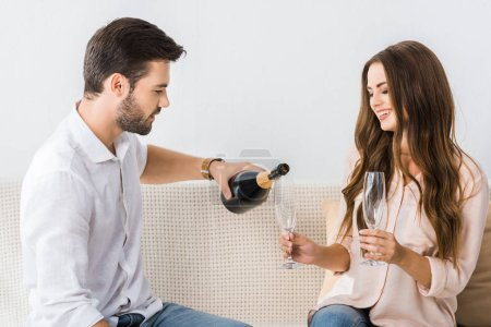 young man pouring champagne into glass while sitting on couch with girlfriend at home