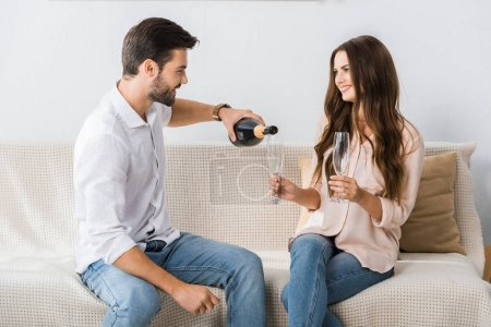 side view of smiling man pouring champagne into glass while sitting on couch with girlfriend at home