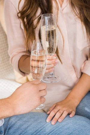 partial view of couple clinking glasses of champagne on sofa at new home