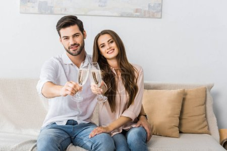 young couple clinking glasses of champagne on sofa at new home
