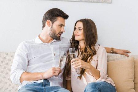 Photo pour Portrait de verres sonnante couple de champagne sur canapé à la nouvelle maison - image libre de droit