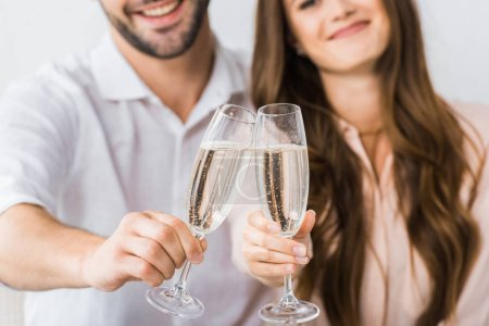 partial view of smiling couple clinking glasses of champagne on sofa at new home