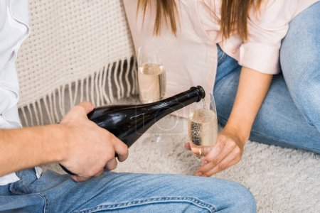 partial view of man pouring champagne into glass while sitting on floor together with girlfriend at home