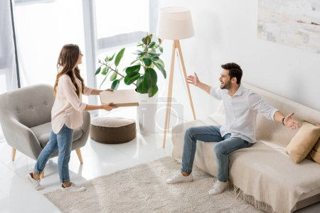 high angle view of young couple with pizza in disposable box at home