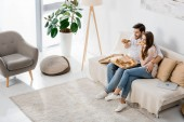 high angle view of young couple eating pizza while watching tv at home