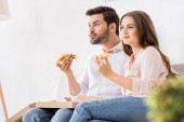 portrait of young couple eating pizza while watching tv at home