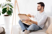 man eating pizza while watching tv alone at home