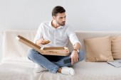 young man with remote control in hand eating pizza alone at home