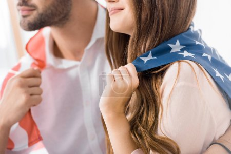 partial view of couple covered with american flag at home