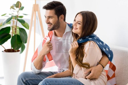 young couple covered with american flag resting on sofa at home