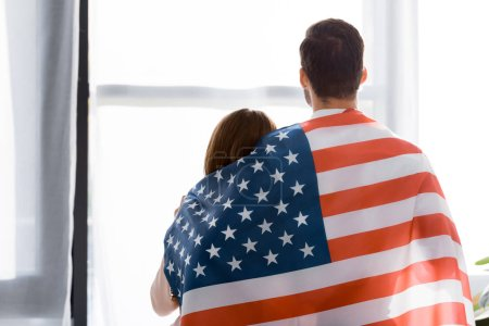 rear view of couple covered with american flag looking out window at home