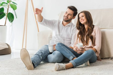 Photo pour Couple d'amoureux heureux avec les tasses de café assis sur le sol et regarder la télévision à la maison - image libre de droit
