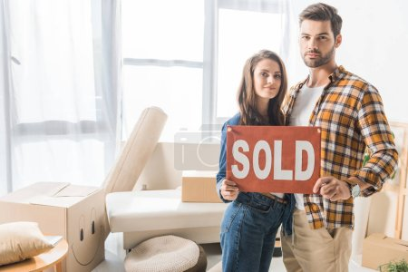 portrait of young couple holding sold red card at home with cardboard boxes