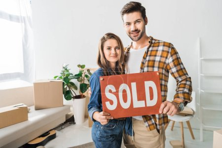 portrait of smiling couple holding sold red card at home with cardboard boxes