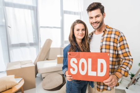 portrait of smiling young couple holding sold red card at home with cardboard boxes