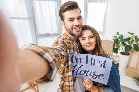 Photo pour Appareil photo point de vue du sourire couple avec notre première maison carte prise selfie ensemble à la nouvelle maison - image libre de droit