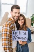portrait of smiling couple with our first house card standing in room with cardboard boxes