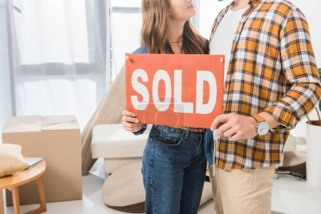 partial view of couple holding sold red card at home with cardboard boxes