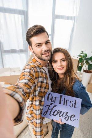 Foto de Cámara punto de vista de la sonriente pareja con nuestra primer casa tarjeta toma selfie junto en nuevo hogar - Imagen libre de derechos