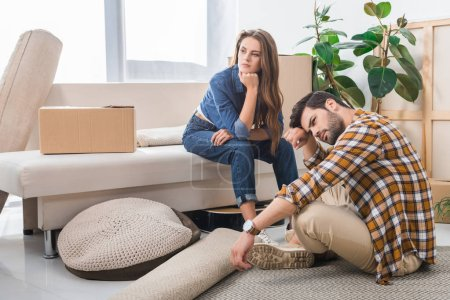 Photo for Pensive young couple at new house with cardboard boxes, moving home concept - Royalty Free Image