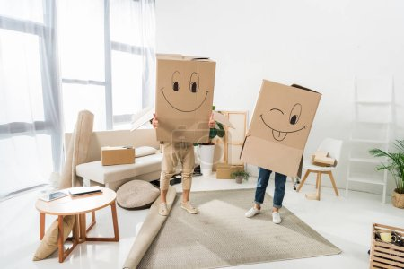 Photo for Obscured view of couple with cardboard boxes on heads at new house, moving home concept - Royalty Free Image