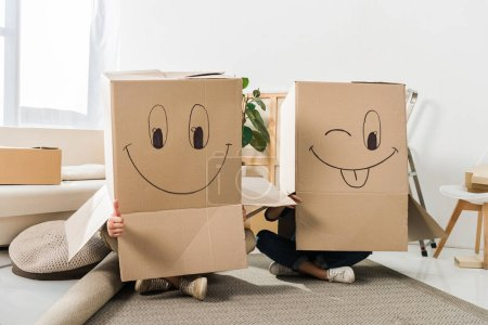 obscured view of couple with cardboard boxes on heads sitting on floor at new house, moving home concept