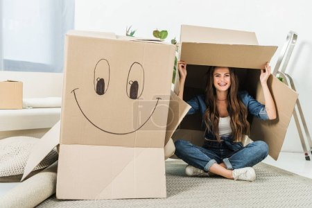 happy woman with cardboard boxes sitting on floor at new home