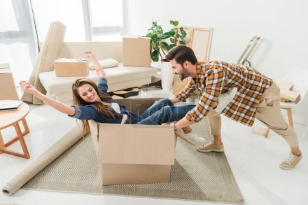 side view of couple having fun with cardboard box at new house, moving home concept