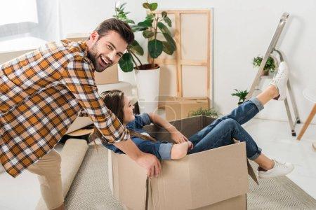 Foto de Vista lateral de la pareja teniendo diversión con caja de cartón en casa nueva, casa concepto en movimiento - Imagen libre de derechos