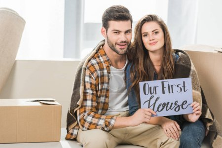 portrait of young couple in blanket with our first house card sitting on sofa, moving home concept