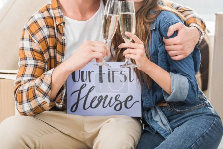 partial view of couple with our first house card clinking glasses of champagne, moving home concept