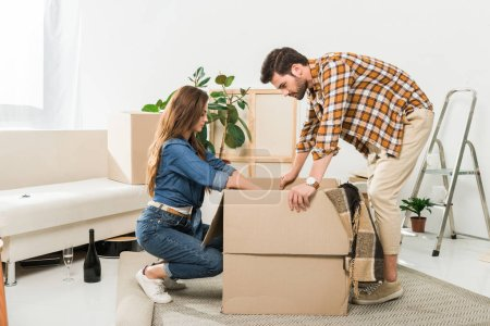 side view of couple unpacking cardboard boxes together at new home, moving home concept