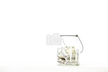 Photo pour Bocal en verre avec billets en dollars isolés sur fond blanc - image libre de droit