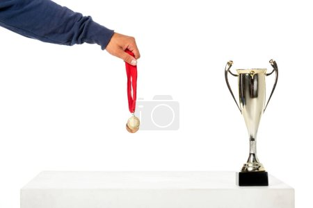 partial view of man holding golden medal near trophy cup isolated on white background
