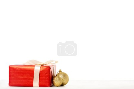 gift box wrapped by ribbon and golden christmas baubles on white background