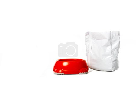 red bowl near package with pet food isolated on white background