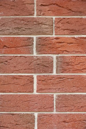 close-up view of red weathered brick wall, textured background