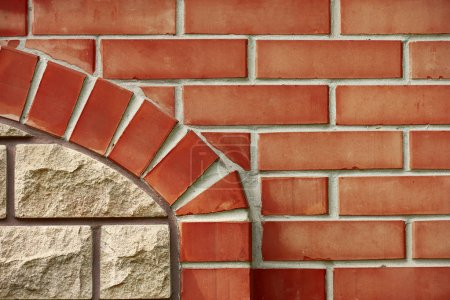 close-up view of red brick wall with brown element, textured background