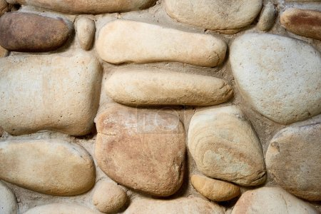 close-up view of rough weathered stone wall texture, full frame background